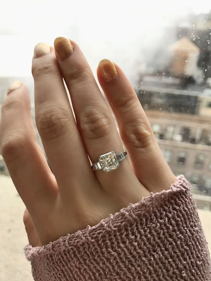 The Amber Ring is a Retro Engagement Ring circa 1945! This ring centers a beautiful Asscher cut diamond weighing 2.37 carats of K-L color, VS2 clarity. The diamond is held in a platinum 4 prong setting. To each side are 4 channel-set baguette cut diamonds that gradually decrease in size. These total approximately 0.60 carats.