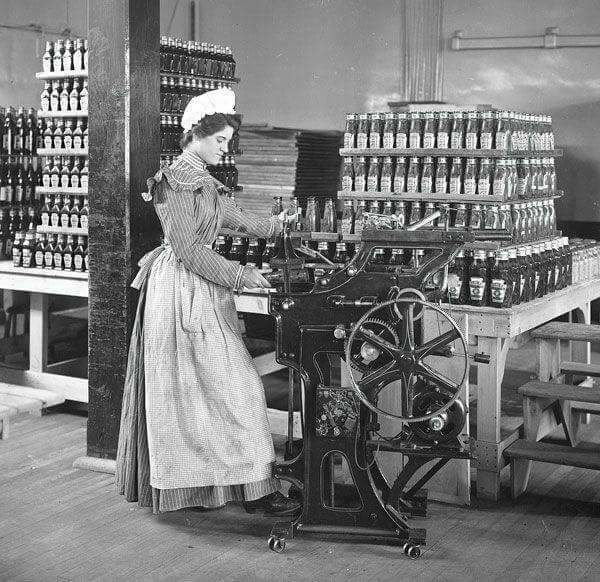 c. 1897, Female worker in Heinz factory, bottling ketchup.