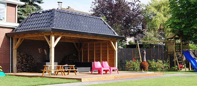 #grote #overkapping op een #verhoogde #houten #vlonder met #loungebanken #picknicktafel #ligstoelen #buitenhaard en ernaast #speeltoestellen. #Kindvriendelijke #tuin   Heart for Gardens.