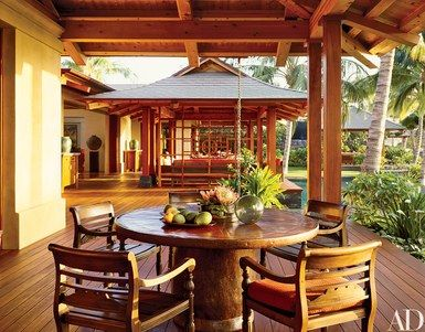 In the outdoor dining area, which looks toward the main lanai, colonial-style chairs from Indonesia are arranged around a table made of found materials | archdigest.com