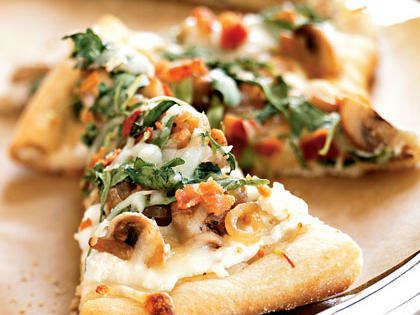 Pizza Bianca with Arugula, Bacon, and Mushrooms RecipeIf you're pressed for time, you can use a store-bought pizza crust instead of making the homemade crust used in this healthy pizza recipe. Topped with bacon and two types of cheese, you would never guess it's only 115 calories per slice.