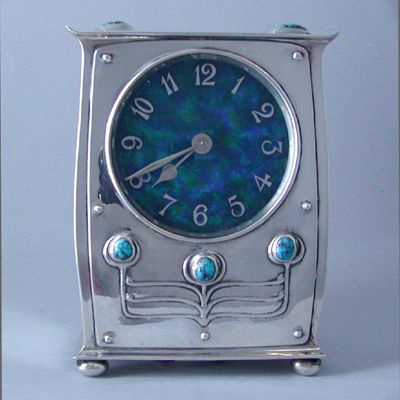 ARCHIBALD KNOX (1864-1933) for LIBERTY & Co. Silver clock, with enamel dial, decorated with stylised buds of turquoise. Size: Height 10.4 cm. Base 8 cm. x 5.2 cm.  Marks for Liberty & Co. Hallmarks for B'ham 1911.