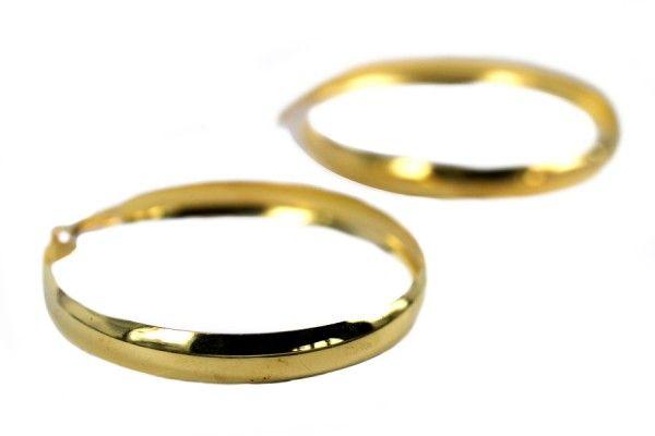 Très belle boucles d'oreilles à double anneaux de couleur dorée. Un bijou de créateur original et