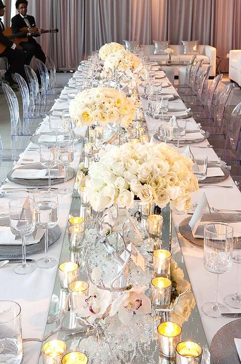 White-on-white centerpieces of roses, orchids and ranunculi reflect on a mirrored runner.