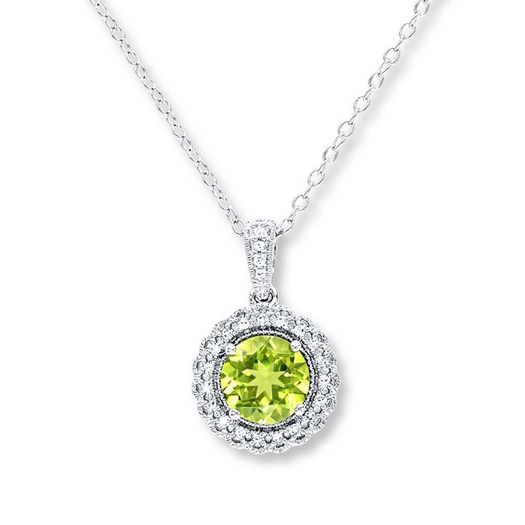 This pretty necklace for her features a round peridot center framed in sparkling round diamonds. Additional diamonds line the bale to complete the look. Styled in sterling silver, the pendant has a total diamond weight of 1/10 carat, and suspends from an 18-inch cable chain that secures with a spring ring clasp. Diamond Total Carat Weight may range from .085 - .11 carats.