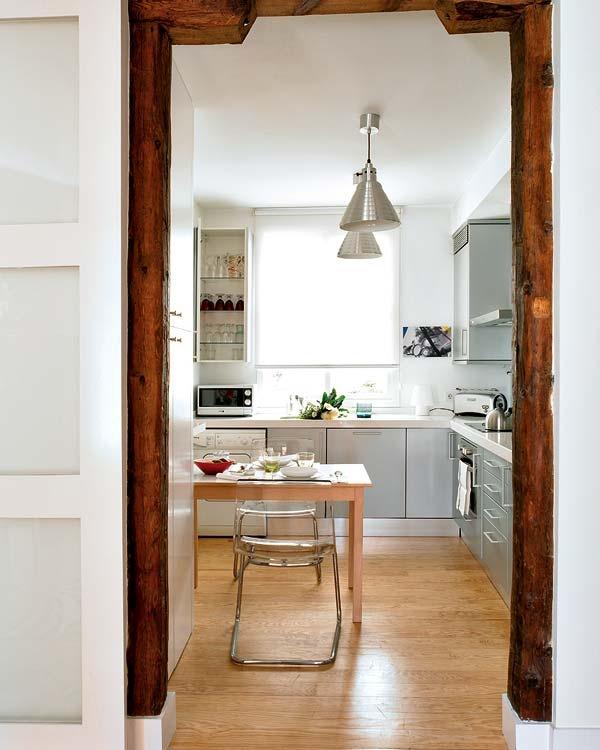 A passagem para a cozinha é feita por um portal bem amplo, com uma porta de correr para isolar o ambiente. Cada espacinho do cômodo é aproveitado com armários, gavetas e prateleiras. O fogão e o forno são embutidos para o melhor aproveitamento da área. Repare que a janela da cozinha a torna mais iluminada e arejada.