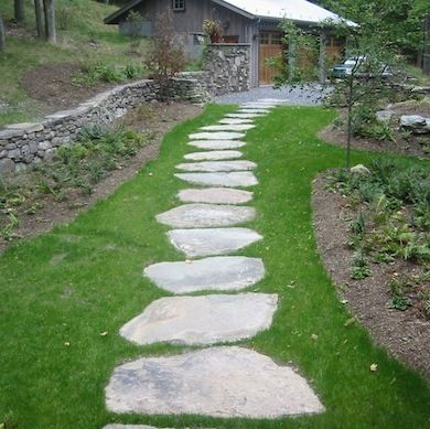 Large stones laid over grass form a casual, comfortable walkway leading through this yard to the garage. Even for beginning DIYers, making astepping-stone walkway like this is an easy weekend project.