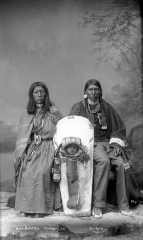 Full-length studio portrait of a Ute Native American family; wife, Ah-Ne-Pitch, is seated at left; baby, Tomas-Cita, is in cradleboard at center; husband, Ma-Riz, is seated at right.