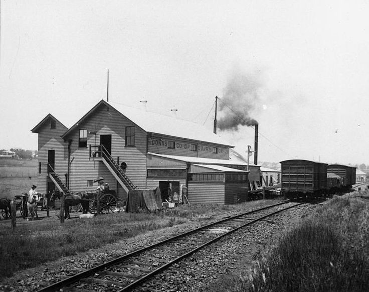 Downs Co-Operative Butter Factory, Toowoomba, ca. 1908. The butter factory is situated next to railway lines and there are several goods carriages waiting on the line. Some horsedrawn vehicles are waiting outside the factory, tended by their owners. Two long flights of steps lead into seperate factory entrances. Smoke is billowing from a chimney of the factory. Date 	circa 1908