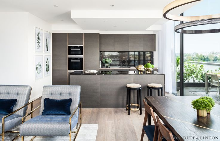 View from our bespoke dining table with brass inlay to the Italian Armony kitchen. We covered the bar stools in a geometric velvet. The worktop and splashback were clad in grey marquina marble. We also covered the brass lounge chairs in a blue and white contemporary herringbone with a twist. #GD&LBespokeFurniture