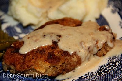 Chicken Fried Steak made with cube steaks, dredged in seasoned flour, fried in fat and bacon drippings and drizzled with a peppered milk gravy.