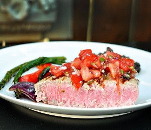 Oven baked tuna with spicy salsa.Tuna steaks with vegetables and spices cooked in halogen oven.