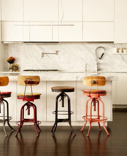 mismatched stools add charming whimsical touch to this all white kitchen!