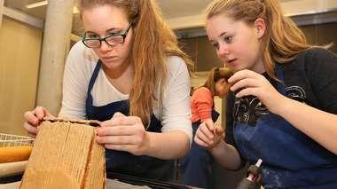 BYGGER POLARIA: Malin Korneliussen (16) og Live Stensrud (16) hadde litt problemer med å bygge Polaria som pepperkakehus, men prøvde å holde motet oppe. (Foto: Ronald Johansen)