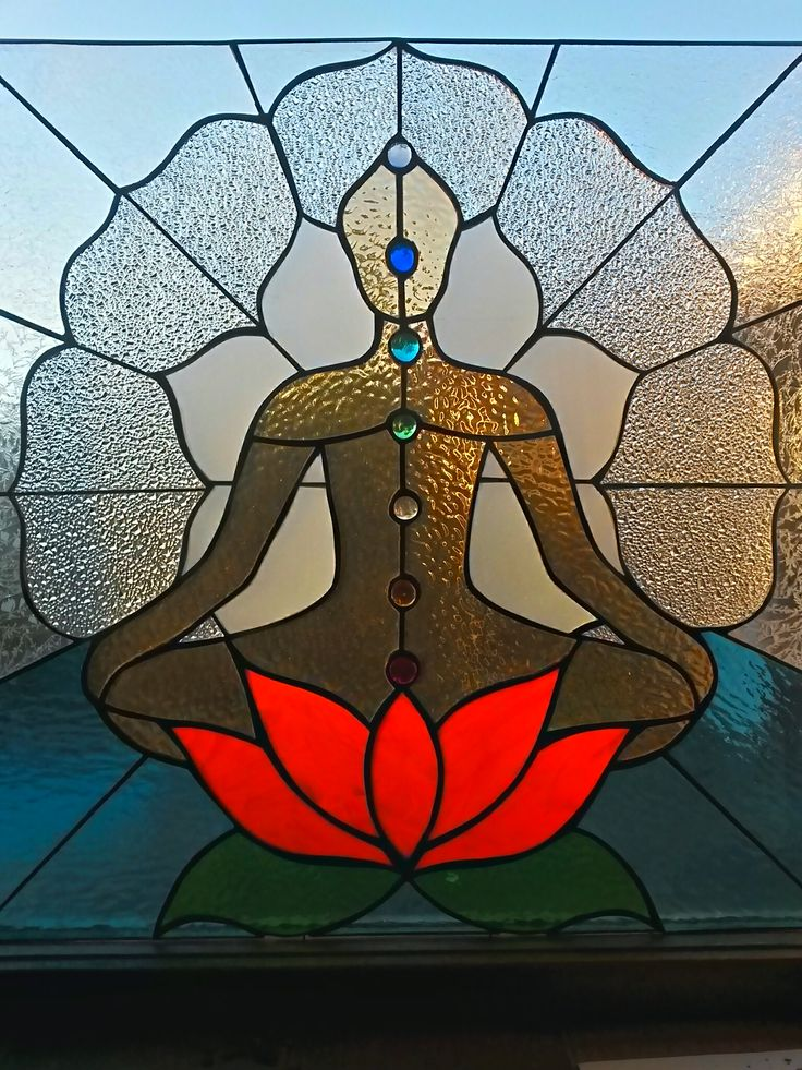 Meditating posture on lotus flower made of stained glass. Energy points known as chakras are depicted within the posture.