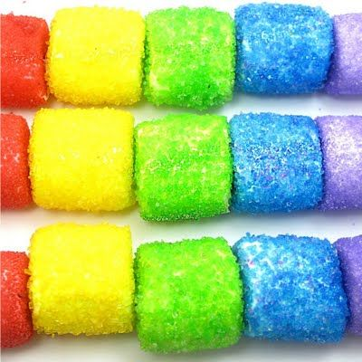 Sparkly Rainbow Marshmallow Kabobs -- You will need:* marshmallows, toothpicks, bowl of water, sprinkles or sanding sugar, variety of colors, wax paper, lollipop sticks 12-inch, paper towels, Crisco -- *I used red, yellow, green, blue and purple sprinkles. I found five marshmallows worked best per stick, so poor orange and indigo got the shaft. Find lollipop sticks in the craft store.