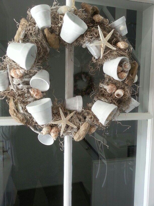 Krans met schelpen en drijfhout en geverfde aardewerk potjes