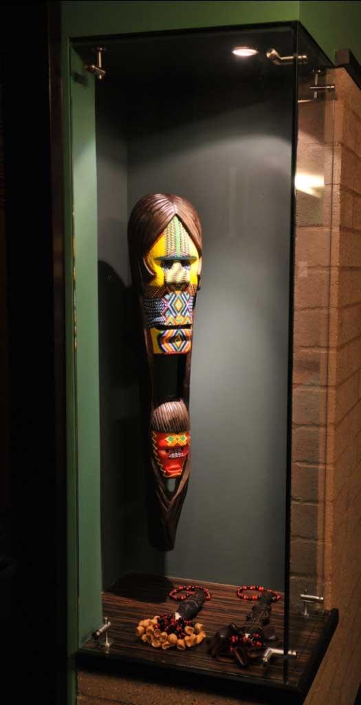 Totem de la maternidad elaborado por la tribu Etnia Camënt¨sá del Amazonas.  Representa el apego entre la madre, el hijo y la tierra.    Verde, etnico, colores, madera, chaquiras, madre, hijo.