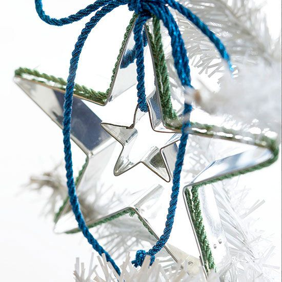 How To: Cookie Cutter Star Ornament.  Using Cookie Cutters in two sizes, dangle the smaller cutter from cording tacked with hot glue from the top of the larger star. Trim the edge with contrasting cording and top with a matching, loose bow.