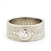 Anne Sporton  Gold bark texture band with a bezel set  White Rose-cut Diamond and pave set Diamonds around the band, 0.62tcw.