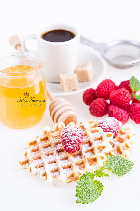 Fresh Belgian waffles with raspberries, honey and cup of coffee on a white background