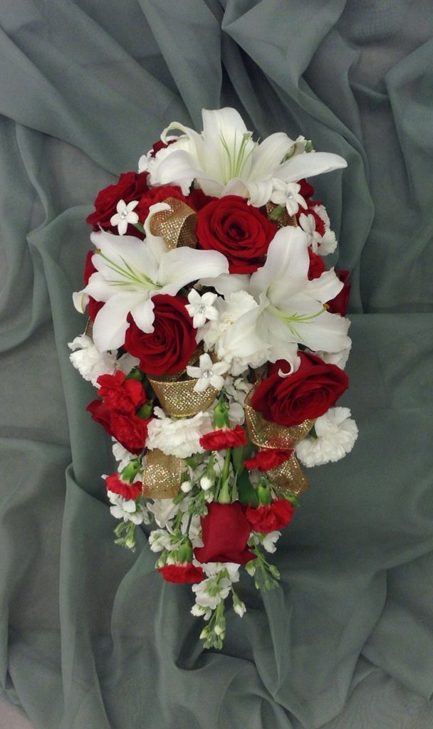 Red and white cascading bridal bouquet with red roses, carnations, lilies, stock, stephanotis and gold ribbon accents by Nancy at Belton hyvee.