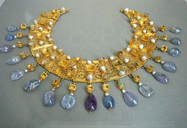 """Byzantine collar in gold with pearls and sapphire cabachons. Altes Museum, Berlin. The Byzantine """"collar"""" is a piece of jewellery sewn onto a textile or gilded leather base similar in style and decoration to the loros, a long, narrow and embroidered scarf which was wrapped around the torso and dropped over the left hand.."""