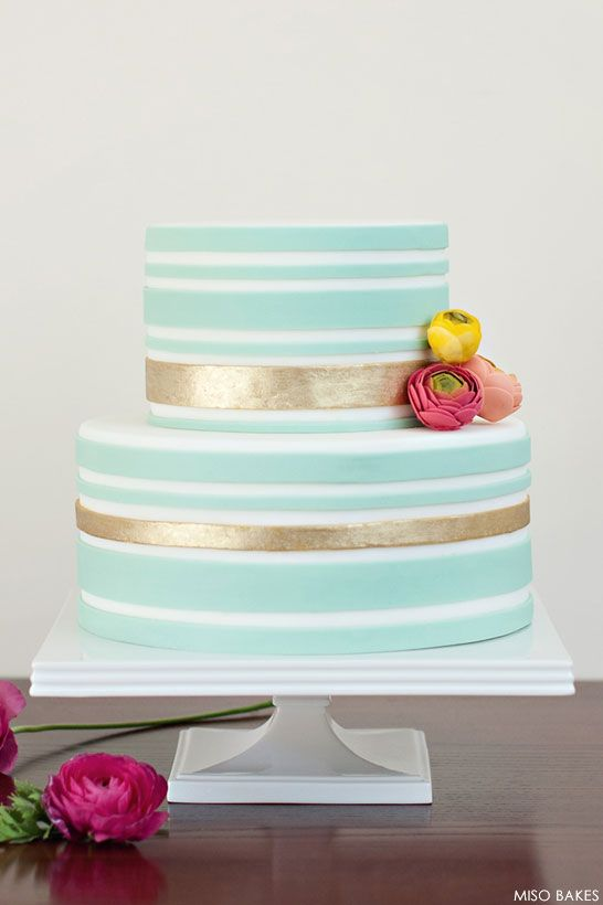 not these colors, but cute style and love these flowers for accent.  Pale Blue & Gold Striped Cake by Miso Bakes