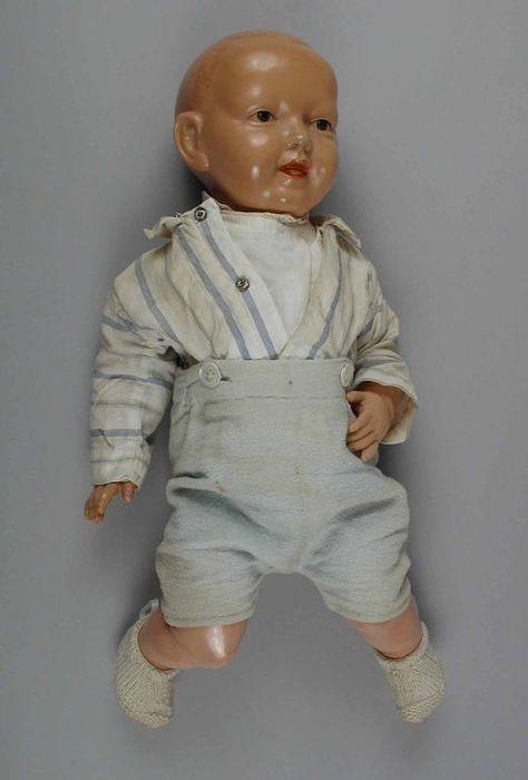 """Pop, jongen, van celluloid, beschilderd gezicht en beweegbare armen en benen, gekleed in wit-blauw hemd met knoopbroekje en witte sokken, """"Schildkröt"""" - Museum Rotterdam"""
