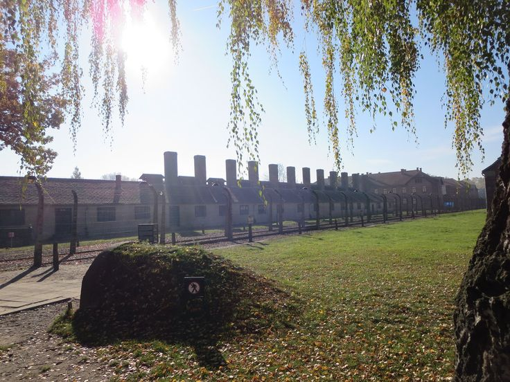In front of the main gate of the Auschwitz I camp. The long building with chimneys is the camp kitchen.