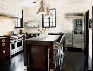 This Gourmet Kitchen Features High End Stainless Steel Appliances, White  Subway Tiles, And Dark Brown Cabinets With Industrial Lighting And Open  Shelves.