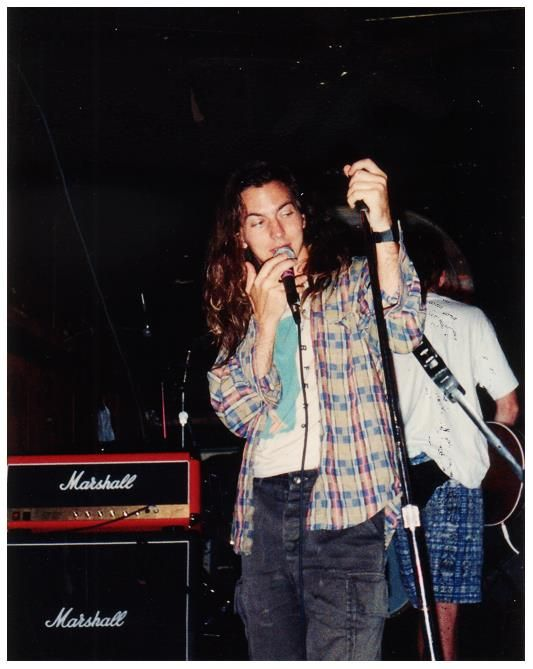 """On December 2, 1991, two days after playing the Roy Wilkins Auditorium in Saint Paul, Minnesota, Pearl Jam rolled into Saint Louis, Missouri, for the first of two nights. The band was touring in support of Ten and shared the bill with the Smashing Pumpkins and the Red Hot Chili Peppers. They played The American Theater to a crowd of 1,500. There is no known setlist for this show.  Photo: Eddie Vedder - July 12, 1991, photo by Tim """"Skully"""" Quinlan from Two Feet Thick."""