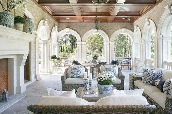 Elegant blue and white decor in furnished loggia of a French chateau (The Enchanted Home). Wood ceiling, grant limestone fireplace, and spectacular arch details.