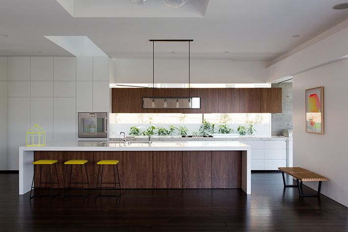 white gloss wall oven and floor to ceiling panels with Smart Stone benchtops and timber laminate