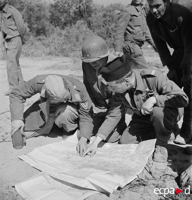 Penché sur une carte d'état-major, un caporal-chef de l'armée de l'air allemande, prisonnier, donne des renseignements à un lieutenant du corps franc d'Afrique (CFA) et à un capitaine de l'armée américaine. Engagés dans la campagne de Tunisie, les soldats du 1er bataillon du CFA, passé sous les ordres du 2e corps d'armée américain le 14 avril 1943 et directement subordonné à la 9e division d'infanterie américaine, se trouvent ici au poste de commandement du colonel Magnan, commandant le CFA…