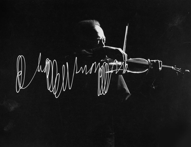 Jascha Heifetz playing violin in Mili's darkened studio as light attached to his bow traces the bow movement.    Photo by Gjon Mili,1952.