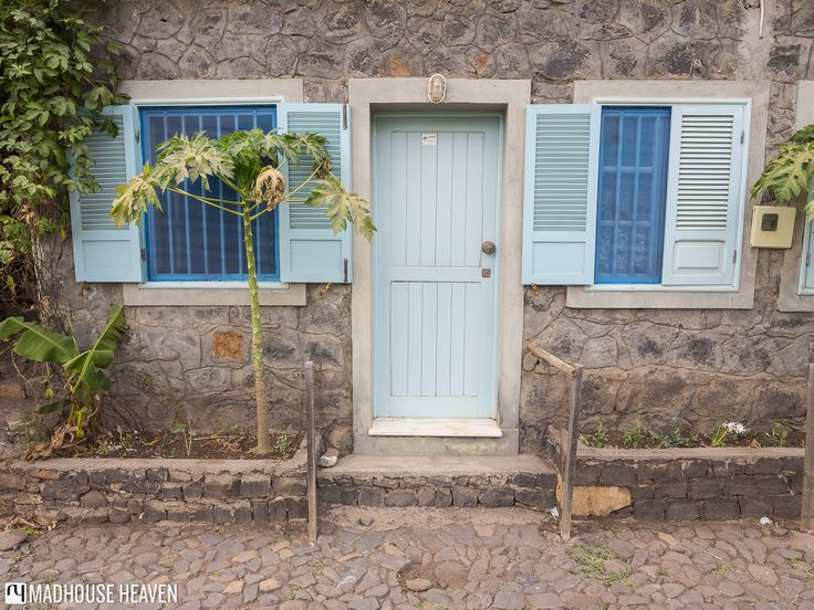 Cute stone houses with blue doors along the Rue des Bananas with small papaya saplings in front, Santiago island, Cape Verde.