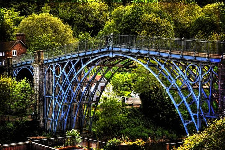The Iron Bridge crosses the River Severn at the Ironbridge Gorge, by the village of Ironbridge, in Shropshire, England. It was the first arch bridge in the world to be made out of cast iron, a material which was previously far too expensive to use for large structures. However, a new blast furnace nearby lowered the cost and so encouraged local engineers and architects to solve a long-standing problem of a crossing over the river. (Wikipedia)