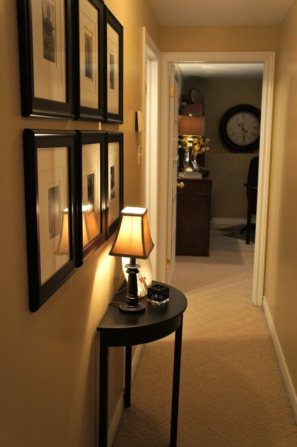 This hallway has a great use of shape.  The six square frames placed in two horzontal lines create flow. They are nicely contrasted by the semi-circle shape of the table and the curved organic shape of the lampshade.