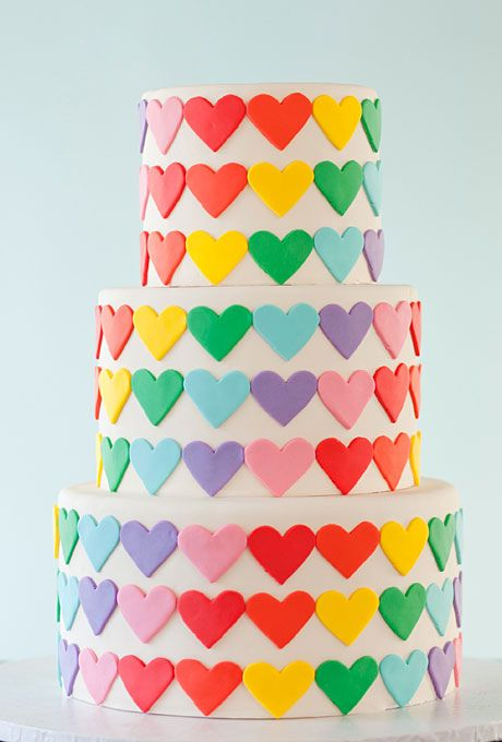 White, round three-tier wedding cake with rainbow hearts. Wild Orchid Baking Co.