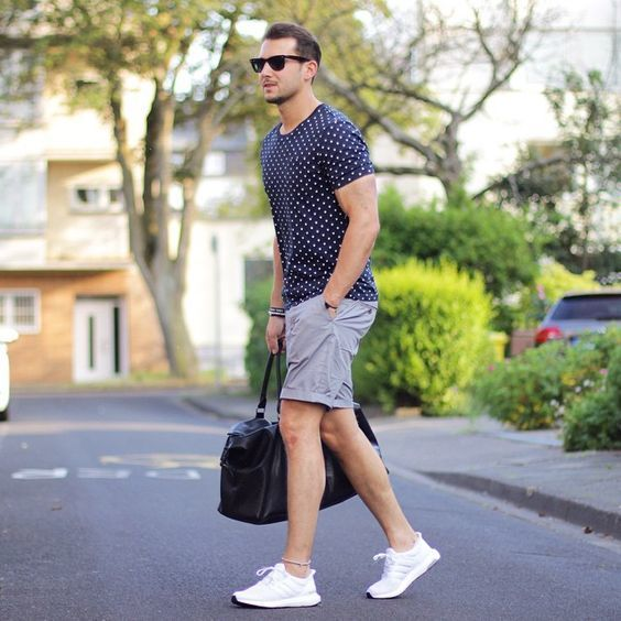 The versatility of a navy blue polka dot crew-neck tee and grey shorts makes them investment-worthy pieces. If you don't want to go all out formal, throw in a pair of white athletic shoes.   Shop this look on Lookastic: https://lookastic.com/men/looks/crew-neck-t-shirt-shorts-athletic-shoes/20257   — Black Sunglasses  — Navy Polka Dot Crew-neck T-shirt  — Navy Bracelet  — Grey Shorts  — Black Leather Holdall  — White Athletic Shoes