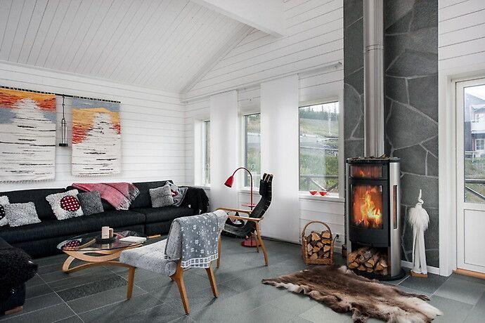 Vardagsrum - Höglekardalen Härligt vardagsrum med träpanel, sten och en inbjudande brasa.