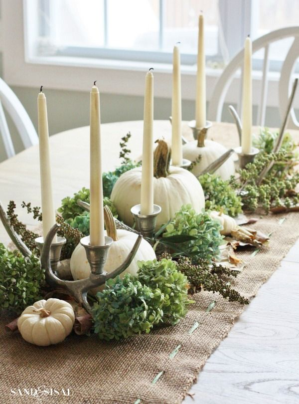 A beautiful fall centerpiece with white pumpkins, dried hydrangea, birch bark and candelabras atop a simple burlap table runner