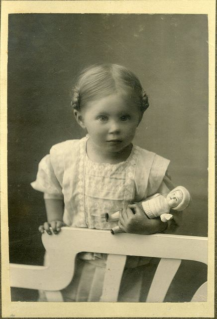 Girl with doll, leaning on back of chair.