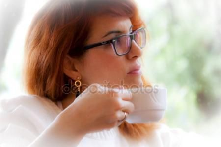 Woman is immersed in her thoughts while holding a cup of tea or coffee — Stock Photo © carlotoffolo #157687980