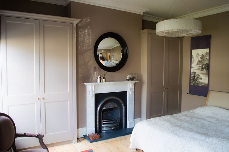 Bespoke fitted wardrobes built into two alcoves in a regency style.