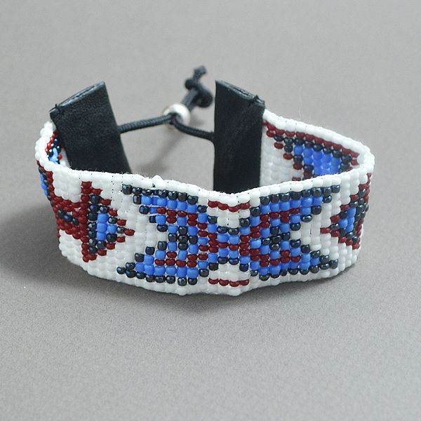 A carefully hand woven beaded bracelet, made ​​of high quality beads. The bracelet is adjustable and the colors used are: Metallic black, white, red &  light blue. The bracelet's dimensions are: 0,98 inches (2,5 cm) in width (13 lines) and 6.3 inches (16 cm) in length.