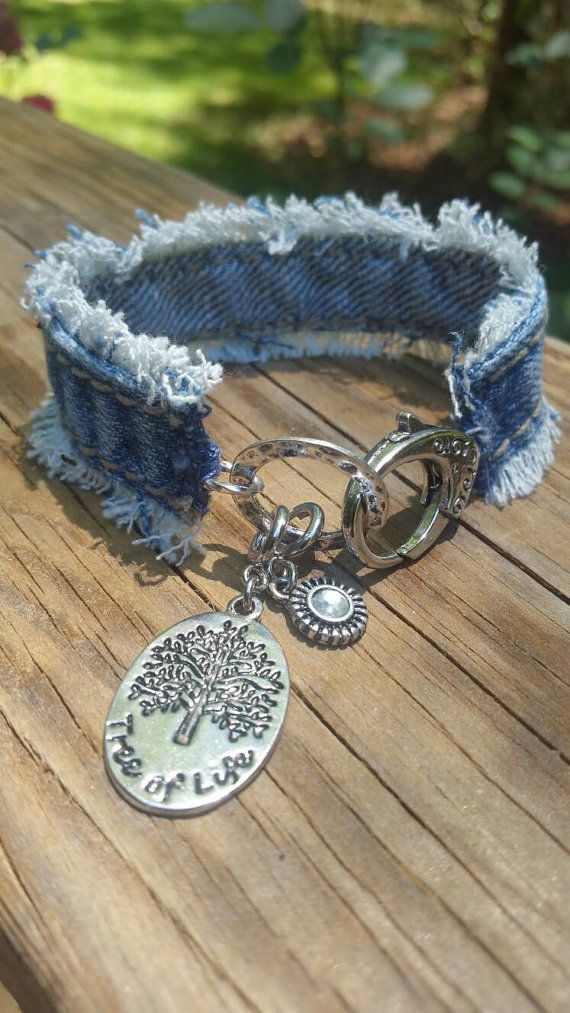 This is a frayed side seam denim bracelet with a large lobster clasp closure. There are two charms, a tree of life and a little bling charm.