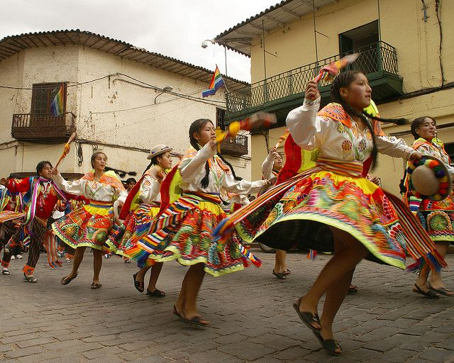 Cuzco, Peru. The women dancing in the streets for a festival. Dressing with special dresses for dancing in the streets. People watching them along the sidewalks.