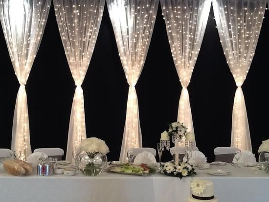 pretty backdrop for the wedding party table tulle and twinkle lights make beautiful wedding decor maybe do a solid white tulle with lights for the whole